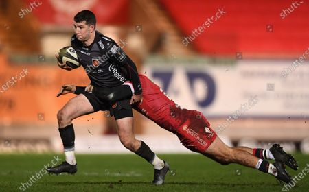 Owen Jenkins of Dragons is tackled by Paul Asquith of Scarlets.