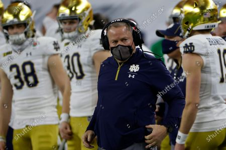 Notre Dame head coach Brian Kelly, center, watches play in the first half of the Rose Bowl NCAA college football game against Alabama in Arlington, Texas