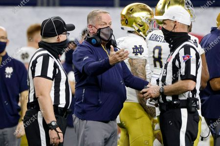 Notre Dame head coach Brian Kelly, center, talks to officials in the first half of the Rose Bowl NCAA college football game against Alabama in Arlington, Texas