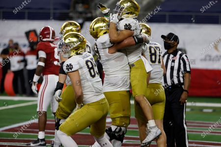Stock Image of Notre Dame running back Kyren Williams, being lifted, celebrates with tight end George Takacn (85) and tight end Michael Mayer (87) and others after scoring a touchdown on a run in the first half of the Rose Bowl NCAA college football game against Alabama in Arlington, Texas