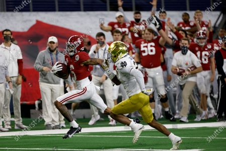 The Alabama sideline erupts in celebration as wide receiver DeVonta Smith (6) sprints to the end zone for a touchdown as Notre Dame safety Shaun Crawford (20) gives chase in the first half of the Rose Bowl NCAA college football game in Arlington, Texas