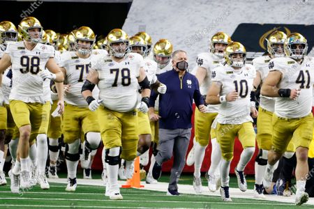 Notre Dame head coach Brian Kelly, center, jogs onto the field alongside his team for at the start of the Rose Bowl NCAA college football game against Alabama in Arlington, Texas