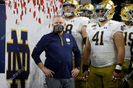 Notre Dame head coach Brian Kelly, left, waits with his team to jog onto the field for their Rose Bowl NCAA college football game against Alabama in Arlington, Texas