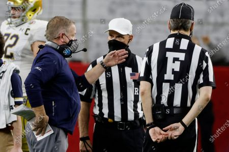 Notre Dame head coach Brian Kelly talks to the officials on the sideline in the second half of the Rose Bowl NCAA college football game against Alabama in Arlington, Texas