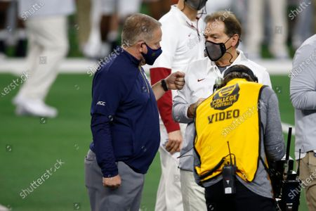 Notre Dame head coach Brian Kelly, left, and Alabama head coach Nick Saban, right, greet each other before the start of the Rose Bowl NCAA college football game in Arlington, Texas