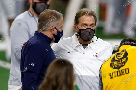 Notre Dame head coach Brian Kelly, left, and Alabama head coach Nick Saban, right, talk to each other before the start of the Rose Bowl NCAA college football game in Arlington, Texas