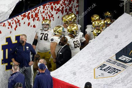 Notre Dame head coach Brian Kelly, left, offensive lineman Tommy Kraemer (78) and other members of the team wait to run onto the field before the start of the Rose Bowl NCAA college football game against Alabama in Arlington, Texas