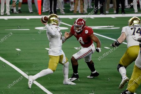 Notre Dame quarterback Ian Book (12) passes the ball under pressure by Alabama linebacker Christopher Allen (4) during the second half of the Rose Bowl NCAA college football game in Arlington, Texas