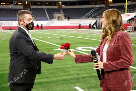 Jason Martin, left, hands roses to ESPN sideline reporter Allison Williams, right, on the field at AT&T Stadium before the Rose Bowl NCAA college football game between Notre Dame and Alabama in Arlington, Texas