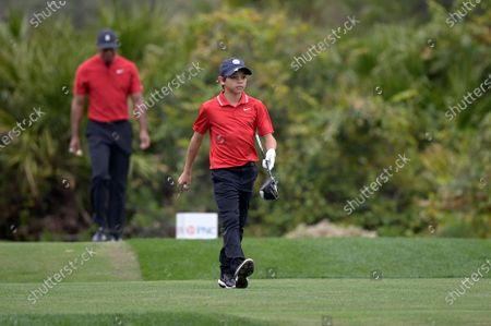 Tiger Woods, left, and his son Charlie walk off the 10th tee during the final round of the PNC Championship golf tournament, in Orlando, Fla