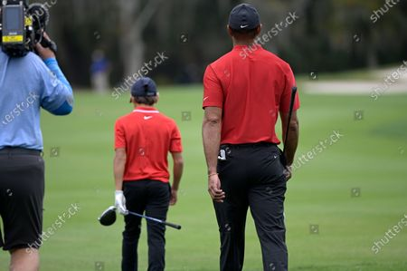 Tiger Woods, right, and his son Charlie walk on the 11th fairway during the final round of the PNC Championship golf tournament, in Orlando, Fla