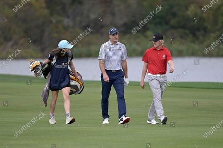 Stock Image of Jim Furyk, center, and his son Tanner, right, walk to the 18th green during the final round of the PNC Championship golf tournament, in Orlando, Fla
