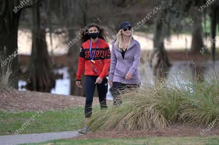 Elin Nordegren, and Sam Alexis Woods, left, follow Tiger Woods and Charlie Woods along the 18th fairway during the final round of the PNC Championship golf tournament, in Orlando, Fla