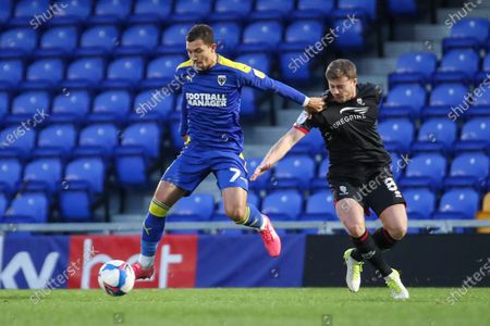 Stock Photo of AFC Wimbledon midfielder Cheye Alexander (7) battles for possession with Lincoln City midfielder James Jones (8) during the EFL Sky Bet League 1 match between AFC Wimbledon and Lincoln City at Plough Lane, London