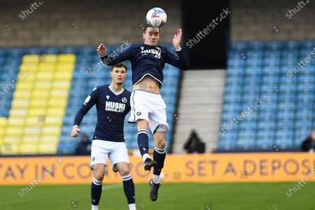 Stock Photo of Millwall midfielder Shaun Williams (6)  heads the ball during the EFL Sky Bet Championship match between Millwall and Coventry City at The Den, London