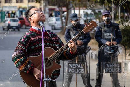 A civil society activist plays a guitar on Streets of Maitighar Mandala as policemen stand on guard during the protest.On December 20, the office of President Bidhya Devi Bhandari announced the dissolution of Parliament at the request of Oliís cabinet, while also anticipating general elections now scheduled for April 30 and May 10, more than a year ahead of schedule.