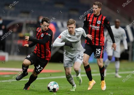 Leverkusen's Mitchell Weiser, center, and Frankfurt's Amin Younes, left, challenge for the ball during a German Bundesliga soccer match between Eintracht Frankfurt and Bayer Leverkusen in Frankfurt, Germany
