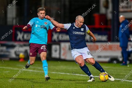 Charlie Adam (#26) of Dundee FC crosses the ball ahead of Jamie Brandon (#25) of Heart of Midlothian FC during the SPFL Championship match between Dundee and Heart of Midlothian at Dens Park, Dundee