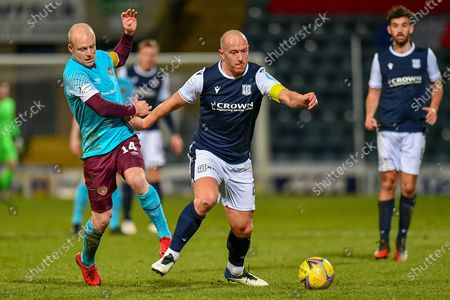 Steven Naismith (#14) of Heart of Midlothian FC tries to pull back Charlie Adam (#26) of Dundee FC during the SPFL Championship match between Dundee and Heart of Midlothian at Dens Park, Dundee