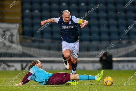 Charlie Adam (#26) of Dundee FC skips over the tackle of Peter Haring (#5) of Heart of Midlothian FC during the SPFL Championship match between Dundee and Heart of Midlothian at Dens Park, Dundee