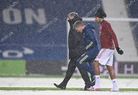 West Bromwich Albion's manager Sam Allardyce, left and Arsenal's Pierre-Emerick Aubameyang walk off the snow covered pitch after speaking to the referee Martin Atkinson ahead of the English Premier League soccer match between West Bromwich Albion and Arsenal at the Hawthorns in Birmingham, England