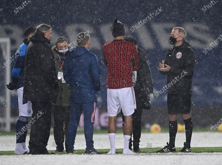 West Bromwich Albion's manager Sam Allardyce, left and Arsenal's Pierre-Emerick Aubameyang center in shorts, speaking to the referee Martin Atkinson, right ahead of the English Premier League soccer match between West Bromwich Albion and Arsenal at the Hawthorns in Birmingham, England