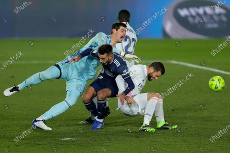 Stock Image of Celta Vigo's Brais Mendez, center, clashes with Real Madrid goalkeeper Thibaut Courtois, left, and Nacho during the Spanish La Liga soccer match between Real Madrid and Celta Vigo at the Alfredo Di Stefano stadium in Madrid, Spain