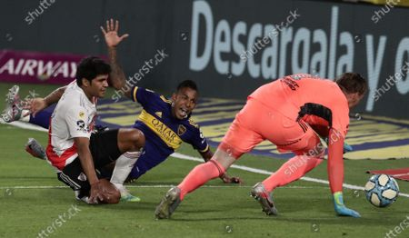 Sebastian Villa (C) of Boca Juniors eyes the ball after kicking between River Plate's goalkeeper Franco Armani (R) and defender Robert Rojas (L), during a Group A Diego Armando Maradona Cup soccer match between Boca Juniors and River Plate, at 'La Bombonera' Stadium, in Buenos Aires, Argentina, 02 January 2021.