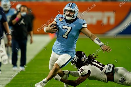 Stock Picture of North Carolina quarterback Sam Howell (7) avoids a tackle by Texas A&M defensive back Brian George (16) during the first half of the Orange Bowl NCAA college football game, in Miami Gardens, Fla