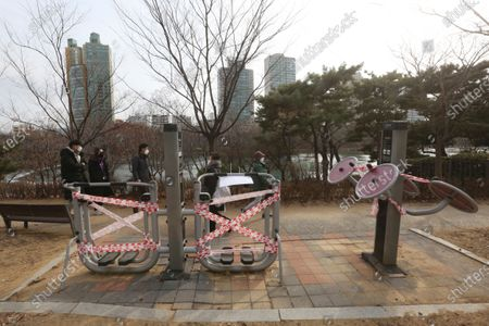 People wearing face masks as a precaution against the coronavirus walk by public sports facilities taped for social distancing rules at a park in Seoul, South Korea