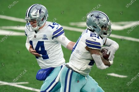 Dallas Cowboys' Andy Dalton, left, hands off to Ezekiel Elliott during the second half of an NFL football game, in East Rutherford, N.J