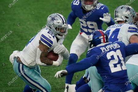 Dallas Cowboys' Ezekiel Elliott, left, runs the ball during the second half of an NFL football game against the New York Giants, in East Rutherford, N.J
