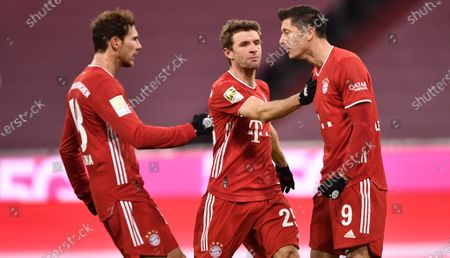 Bayern's Robert Lewandowski (R) celebrates scoring the fourth goal with Bayern's Leon Goretzka (L) and Bayern's Thomas Mueller (C) during the German Bundesliga soccer match between FC Bayern Muenchen and 1. FSV Mainz 05 at Allianz Arena in Munich, Germany, 03 January 2021.