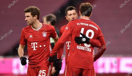 Bayern's Robert Lewandowski (C) celebrates scoring the fourth goal with Bayern's Leon Goretzka (R) and Bayern's Thomas Mueller (L) during the German Bundesliga soccer match between FC Bayern Muenchen and 1. FSV Mainz 05 at Allianz Arena in Munich, Germany, 03 January 2021.