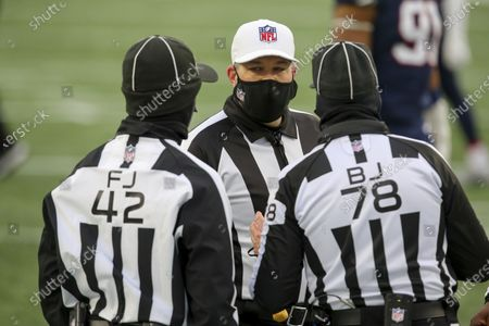 Referee Brad Rogers (126) talks with field judge Nathan Jones (42) and back judge Greg Meyer (78) during an NFL football game between the New England Patriots and the New York Jets, in Foxborough, Mass