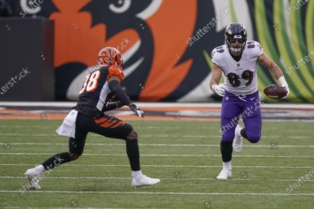 Baltimore Ravens tight end Mark Andrews (89) runs after making a catch as Cincinnati Bengals cornerback LeShaun Sims (38) pursues during the first half of an NFL football game, in Cincinnati