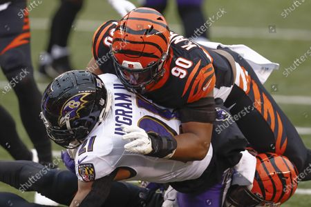 Cincinnati Bengals defensive end Khalid Kareem (90) tackles Baltimore Ravens running back Mark Ingram (21) during the second half of an NFL football game, in Cincinnati