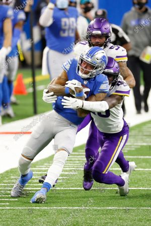 Detroit Lions wide receiver Marvin Jones (11) is tackled by Minnesota Vikings cornerback Jeff Gladney (20) in the first half during an NFL football game, in Detroit