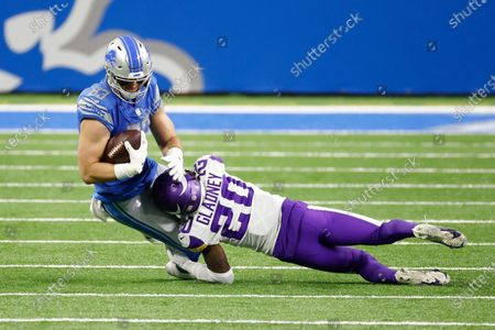 Stock Photo of Detroit Lions tight end Jesse James (83) is tackled by Minnesota Vikings cornerback Jeff Gladney (20) in the first half during an NFL football game, in Detroit