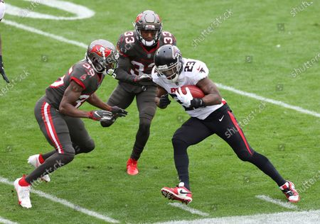 Atlanta Falcons running back Brian Hill (23) runs at Tampa Bay Buccaneers cornerback Jamel Dean (35) and free safety Jordan Whitehead (33) during the first half of an NFL football game, in Tampa, Fla