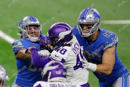 Stock Image of Detroit Lions tight end Hunter Bryant, left, and tight end Jesse James (83) tackle Minnesota Vikings linebacker Blake Lynch (48) during the second half of an NFL football game, in Detroit