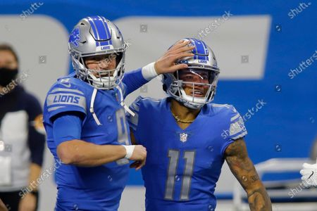Detroit Lions quarterback Matthew Stafford (9) pats wide receiver Marvin Jones (11) after Jones' touchdown during the first half of an NFL football game against the Minnesota Vikings, in Detroit