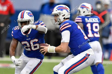 Buffalo Bills quarterback Josh Allen (17) fakes a handoff to running back Devin Singletary (26) during the first half of an NFL football game against the Miami Dolphins, in Orchard Park, N.Y
