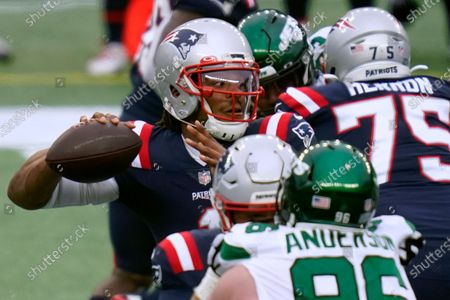 New England Patriots quarterback Cam Newton passes under pressure from New York Jets defensive end Henry Anderson in the first half of an NFL football game, in Foxborough, Mass
