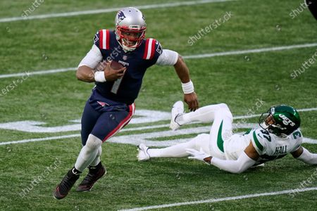 New England Patriots quarterback Cam Newton runs from New York Jets cornerback Bryce Hall in the second half of an NFL football game, in Foxborough, Mass