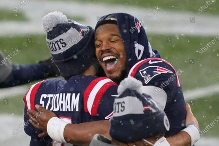 New England Patriots quarterbacks Jarrett Stidham, left, and Cam Newton embrace on the sideline at the end of an NFL football game against the New York Jets, in Foxborough, Mass