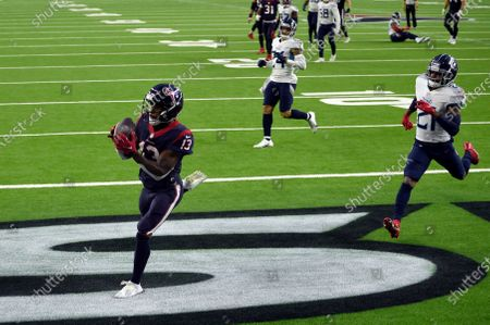 Houston Texans wide receiver Brandin Cooks (13) catches a touchdown pass as Tennessee Titans cornerback Malcolm Butler (21) defends during the second half of an NFL football game, in Houston