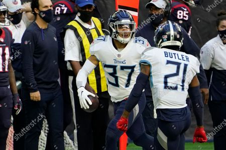 Tennessee Titans strong safety Amani Hooker (37) celebrates with Malcolm Butler (21) after intercepting a pass against the Houston Texans during the first half of an NFL football game, in Houston