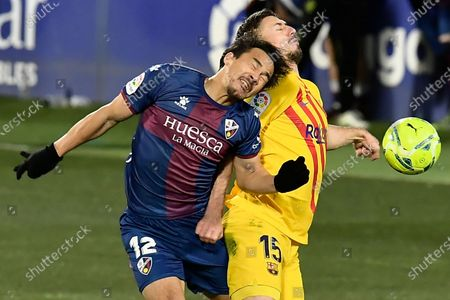 Huesca's Shinji Okazaki, left, vies for the ball with Barcelona's Clement Lenglet during the Spanish La Liga soccer match between Huesca and FC Barcelona at El Alcoraz stadium in Huesca, Spain