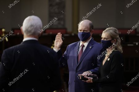 Stock Image of Senator Christopher A. Coons, a Democrat from Delaware, center, wears a protective mask while being ceremoniously sworn-in by U.S. Vice President Mike Pence, left, with wife Annie Coons, right, at the U.S. Capitol in Washington, DC on Sunday, January 3, 2021. The 117th Congress begins today with the election of the speaker of the House and administration of the oath of office for lawmakers in both chambers, procedures that will be modified to account for Covid-19 precautions.